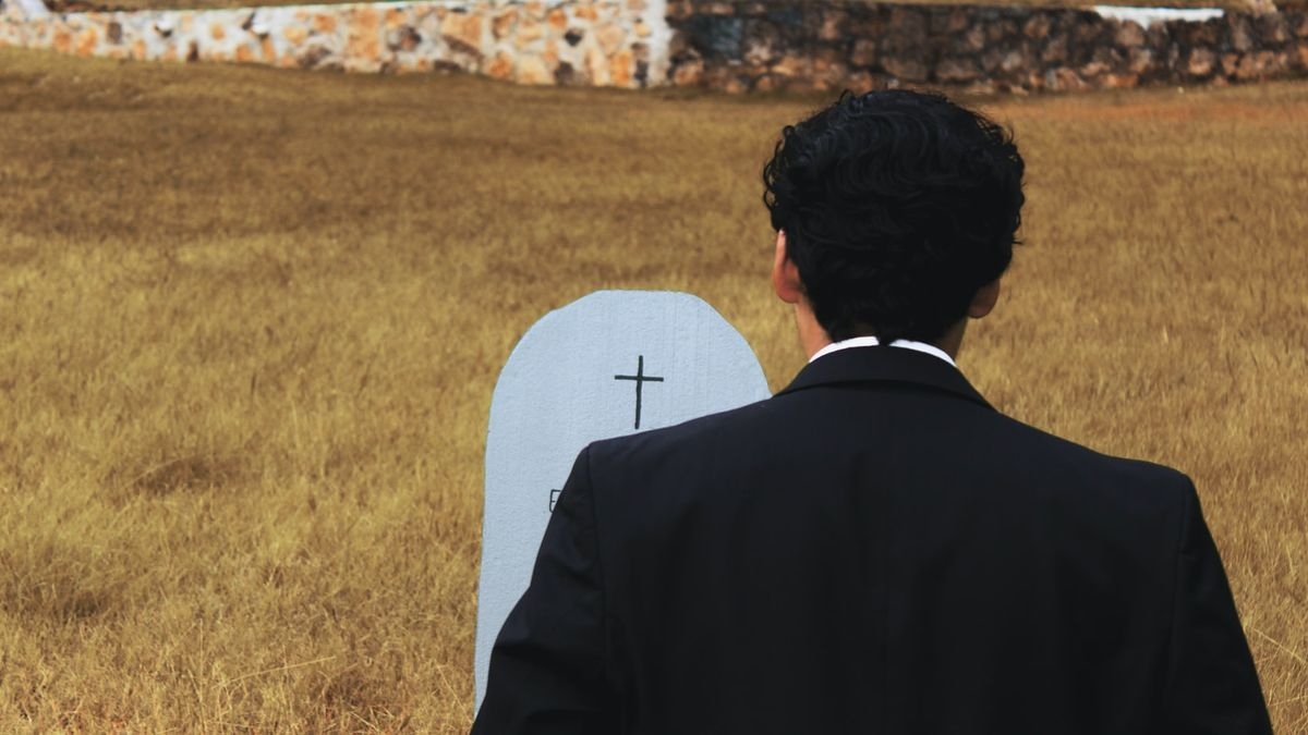 Un hombre ante una tumba