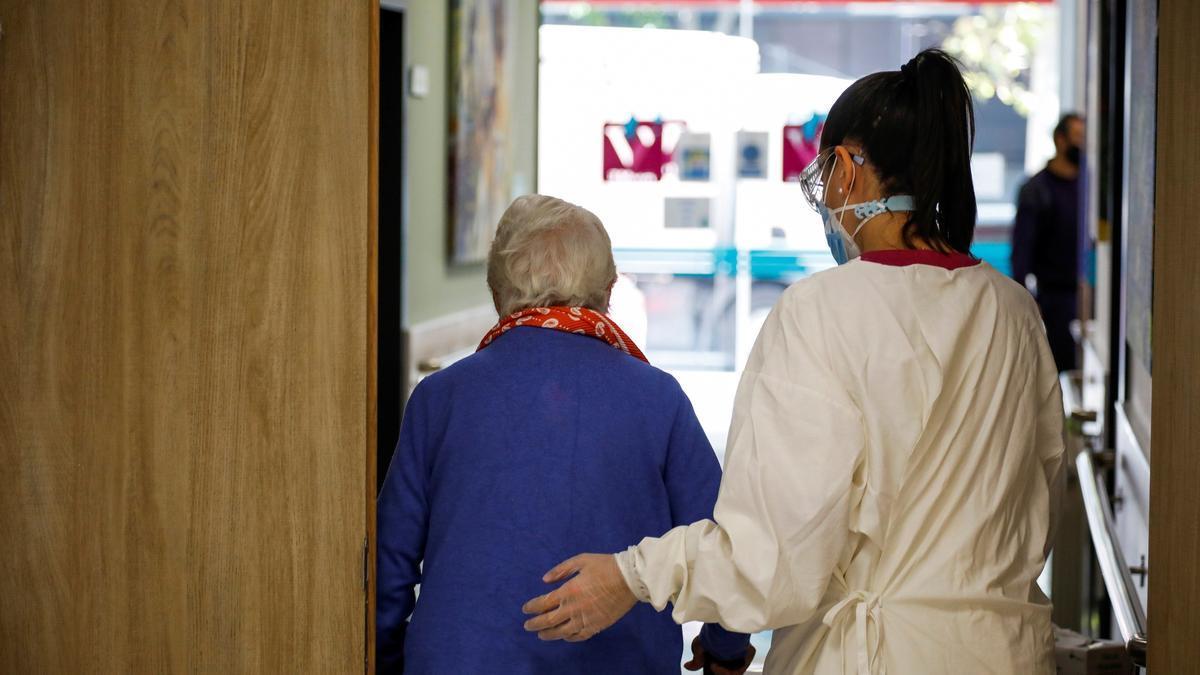 Una trabajadora de una residencia de mayores ayuda a una paciente