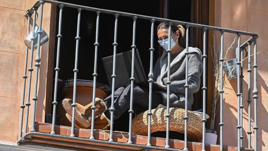 Una mujer en el balcón de su vivienda.