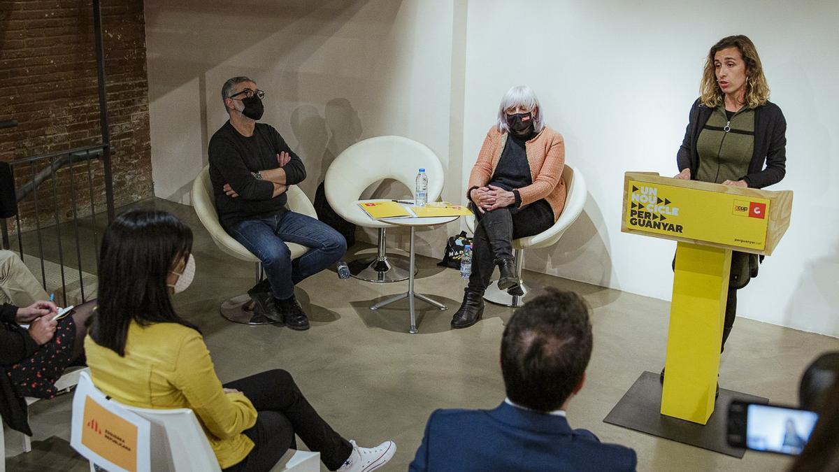 Laia Estrada, en el atril, junto a los diputados Carles Riera y Dolors Sabater, durante la conferencia