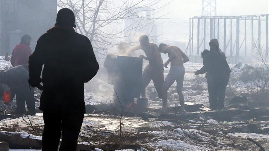 Refugiados hierven agua en un asentamiento de Belgrado