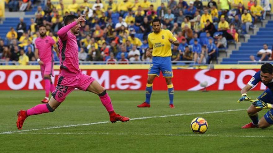 El portero de la UD Las Palmas Raúl Lizoaín (d) se dispone a detener un balón ante Jason (i), del Levante.