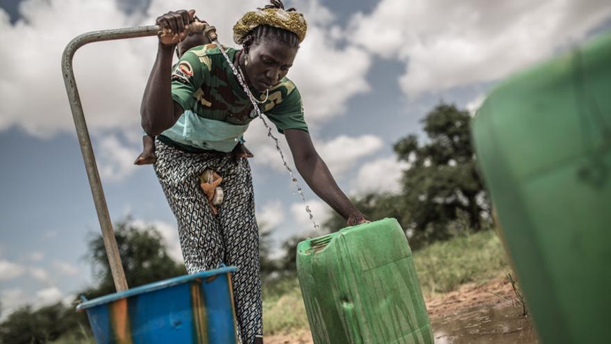 Una mujer en el pueblo de Kario, en el centro de Burkina Faso (África Occidental), llena un bidón de agua potable del grifo alimentado por una torre de agua que han instalado en su comunidad