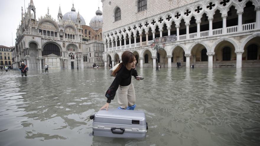 Una turista recoge su maleta flotando del agua