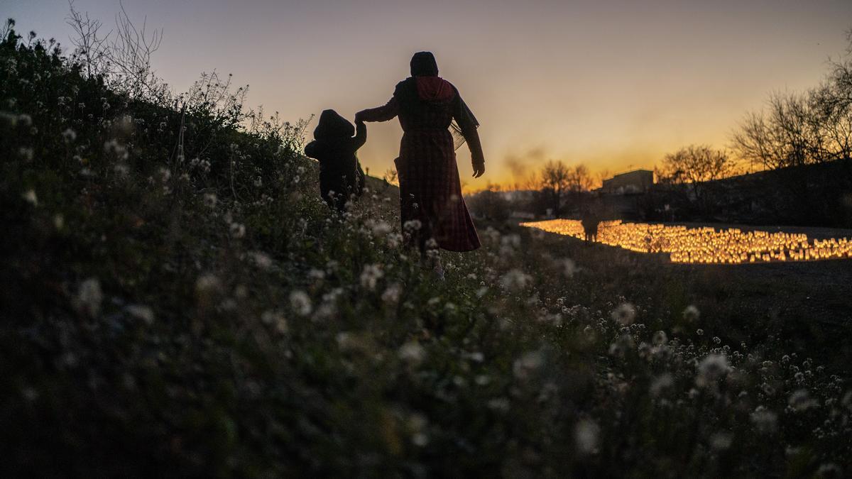 Una mujer lleva a un niño de la mano la víspera de Reyes en la Cañada Real