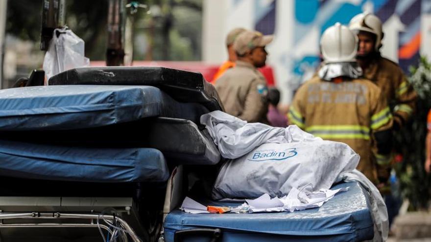 Bomberos trabajan en la entrada del hospital privado donde se registró un incendio en la tarde del jueves, en el barrio Maracaná de Río de Janeiro (Braisl).