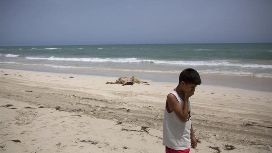Un niño camina junto a los cuerpos sin vida de inmigrantes que han aparecido en una playa en Zuwarah al oeste de Trípoli en Libia | FOTO: EFE