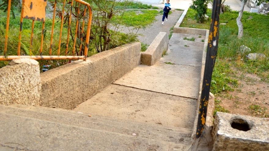 La falta de barandillas en las escaleras obliga a los vecinos a crearlas con vallas de obras. FOTO: Iago Otero Paz.