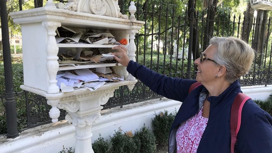 Una mujer coloca una carta en el anaquel con un mensaje dedicado al poeta.
