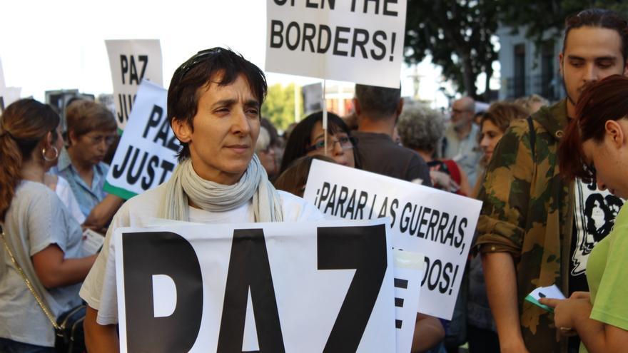 Una manifestante sostiene una pancarta durante la marcha en apoyo a los refugiados hoy en Madrid. Foto: Alberto Ortiz