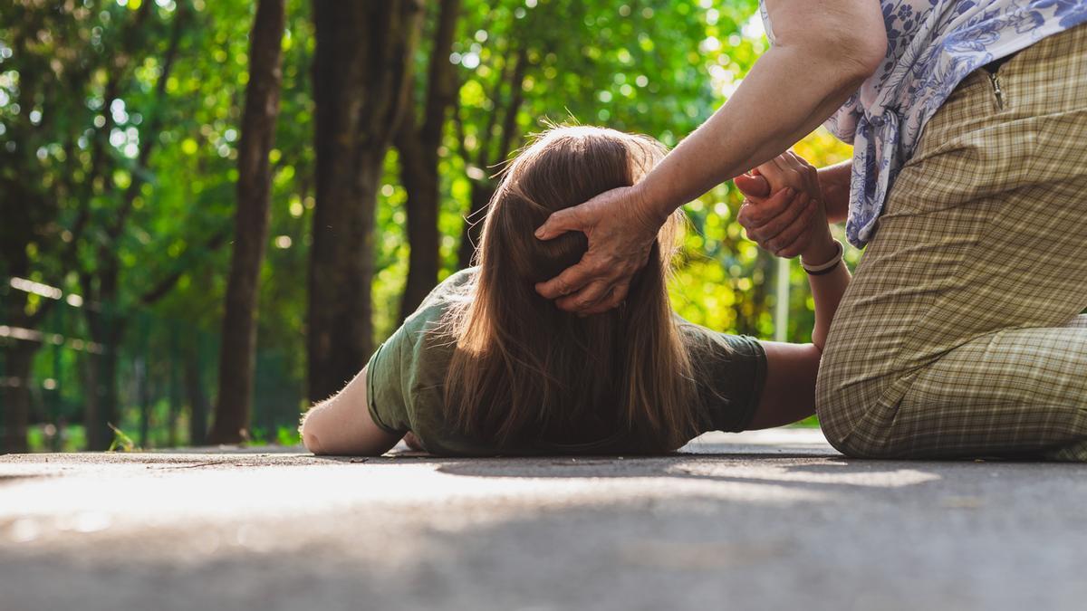 Una mujer ayuda a una joven con una crisis de epilepsia.