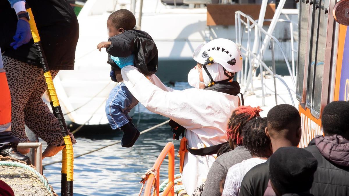 Un tripulante de Salvamento Marítimo desembarca a un menor en el muelle de Arguineguín tras ser rescatado junto a más de 80 migrantes, que iban a bordo de dos pateras al sur de Gran Canaria este viernes 17 de septiembre.