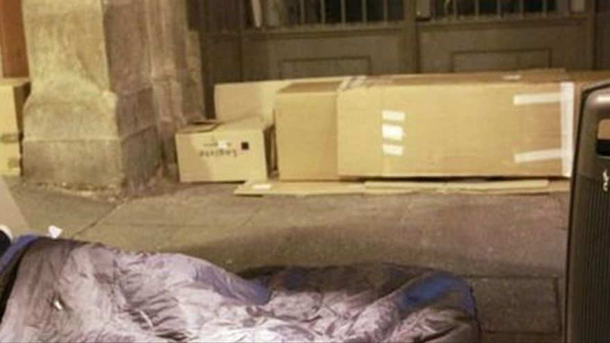 Un 'sin techo' (ajeno a la información) se cobija bajo unas cartones para pasar la noche.