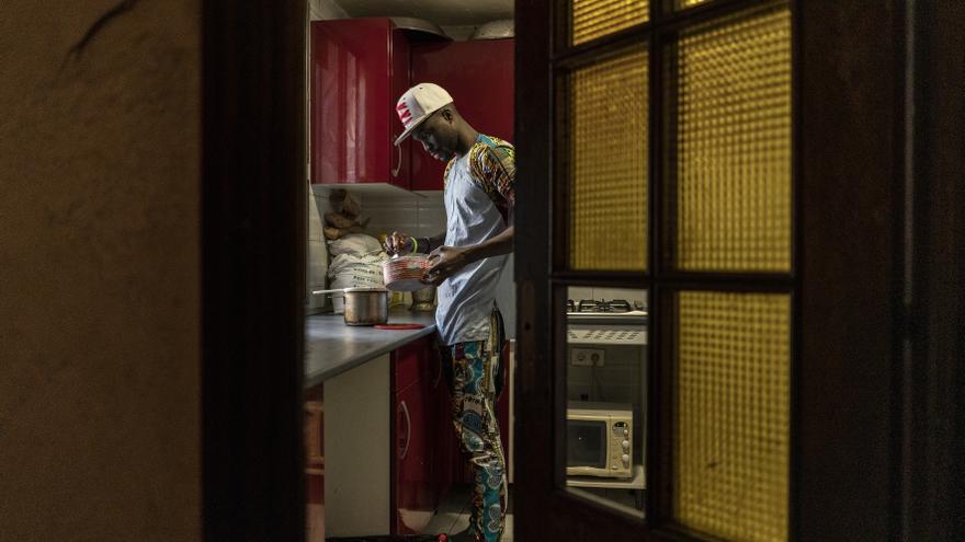 Un joven senegalés confinado, que se dedica a la venta ambulante, prepara un café en su casa del barrio madrileño de Lavapiés.