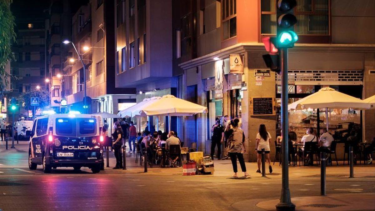 La Policía vigila que se cumplan las medidas frente a la COVID-19 en una calle de Las Palmas de Gran Canaria