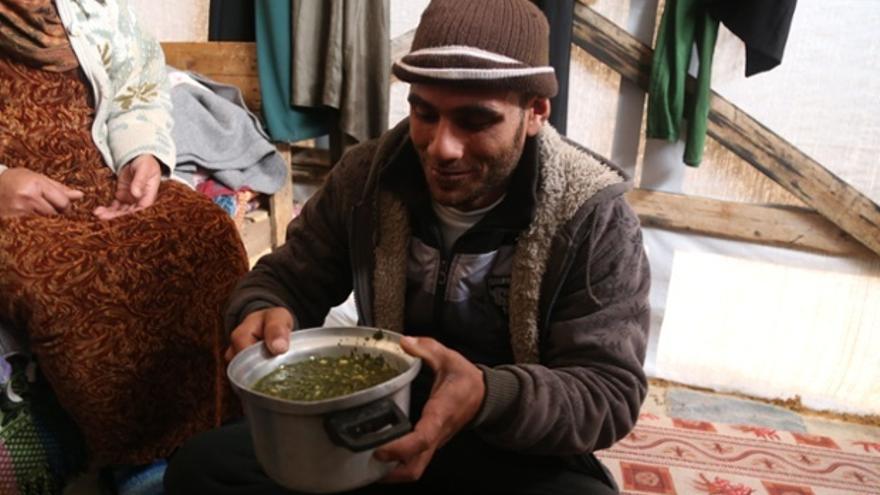 El tío de Salma con la sopa de hierba silvestre que constituye la mayor parte de la dieta de la familia.  Fotografía: Belal Hasna