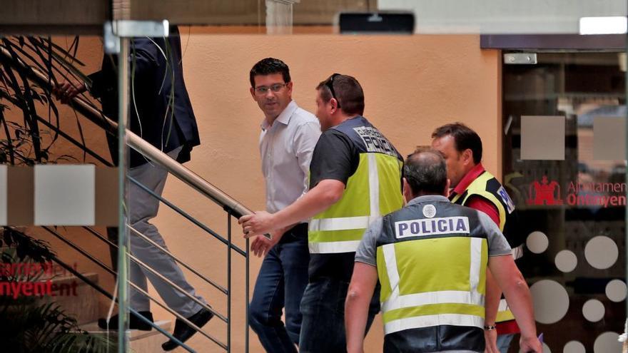 El expresidente de la Diputación de Valencia, Jorge Rodríguez, acompañado por agentes de la policía durante el desarrollo de la operación Alquería