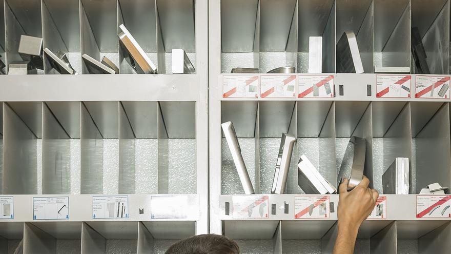 Un empleado de ADM Tech, junto a una estantería con piezas aeronáuticas