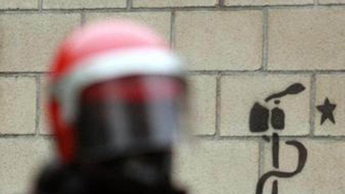 Un agente de la Ertzaintza, junto a una pintada de ETA
