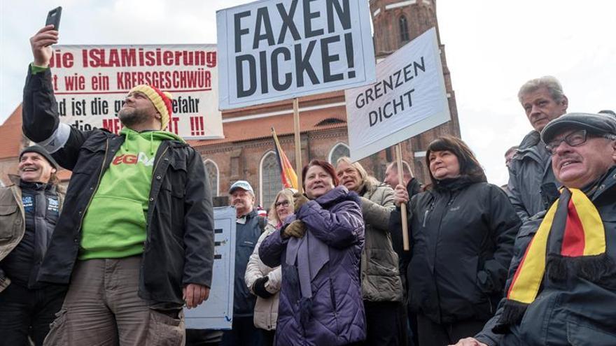 Manifestantes sostienen carteles en el que se puede leer 'Faxen Dicke' (Ya tenemos suficiente), 'Grenzen Dicht' (Cerrar las fronteras) asisten a una manifestación del grupo de ultraderecha Patria Futura en Cottbus, Alemania, el 03 de febrero de 2018.