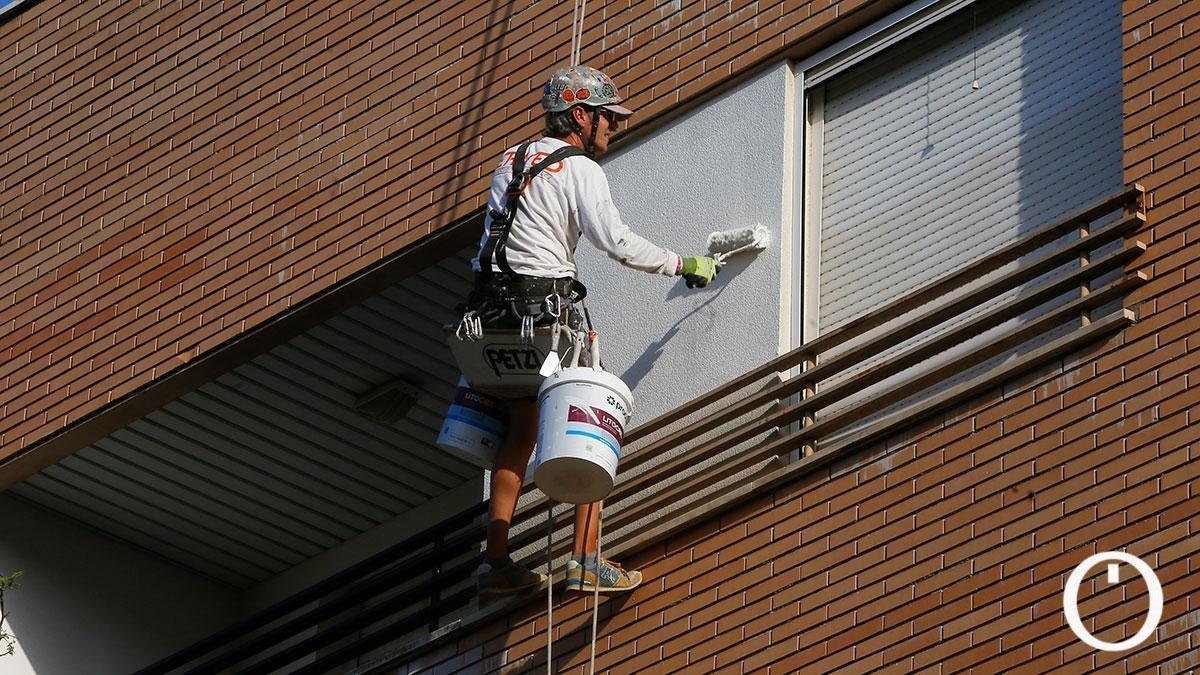 Un pintor en vertical pintando una fachada
