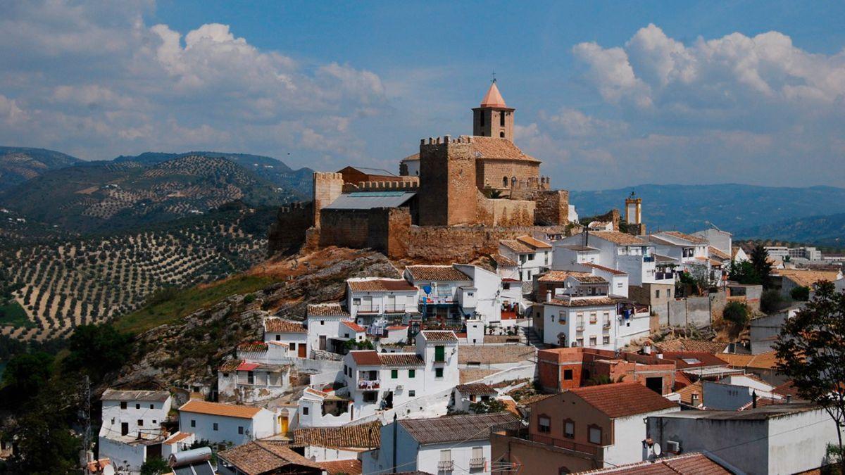 Vista del castillo y el pueblo de Iznájar, entre campos de olivos.