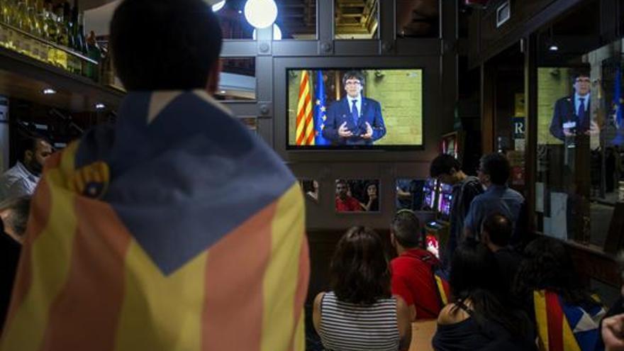 Un grupo de ciudadanos siguen desde una pantalla de televisión la declaración institucional del presidente de la Generalitat, Carles Puigdemont, tras la decisión del Gobierno de aplicar el artículo 155 en Cataluña