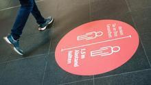 Cartel informativo sobre la necesaria distancia de seguridad frente al coronavirus en el suelo de una estación de tren de Berlín EFE/EPA/CLEMENS BILAN