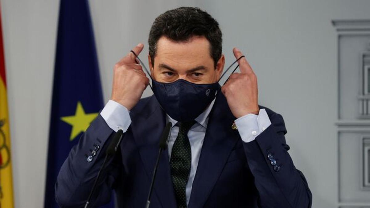 El presidente de la Junta, colocándose una mascarilla en una comparecencia
