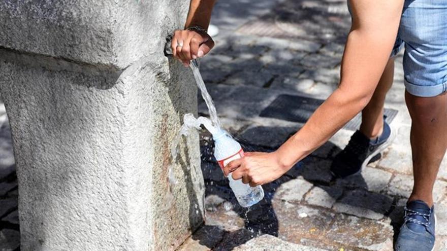 Un hombre coge agua en una fuente.
