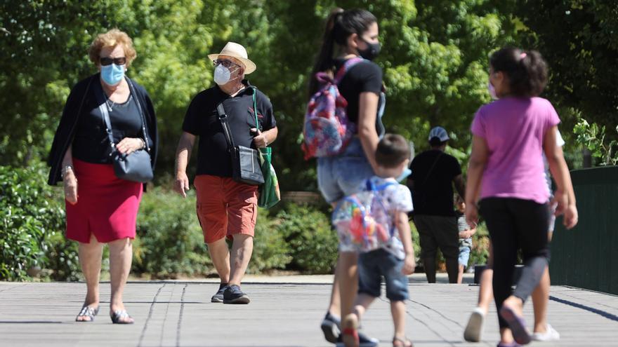 Niños y adultos pasean por la calle con mascarilla