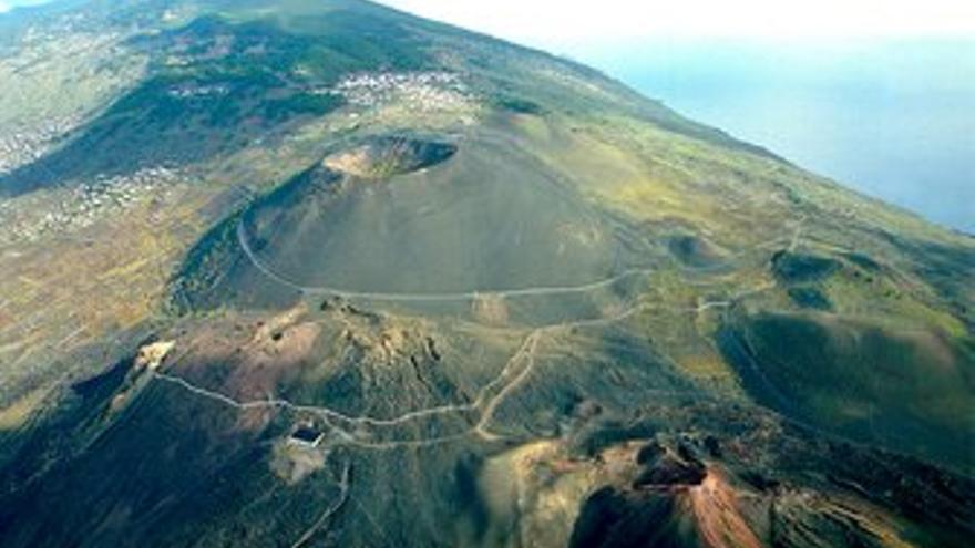ARRIBA: Vista área del municipio de Fuencaliente con los volcanes San Antonio y Teneguía, en primer término, y viñedos. ABAJO: Un grupo de personas vendimian en La Palma.