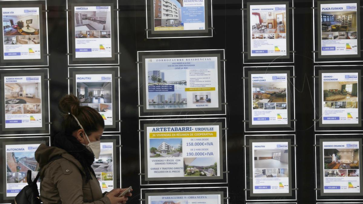 Una mujer pasa por delante de un portal inmobiliario de venta y alquiler.