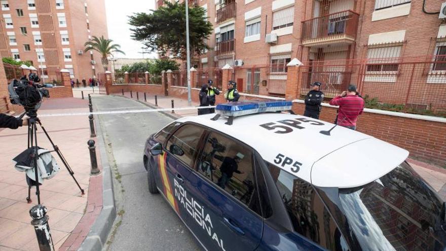 Agentes de la policía nacional y local en la entrada del edificio donde murió la víctima.