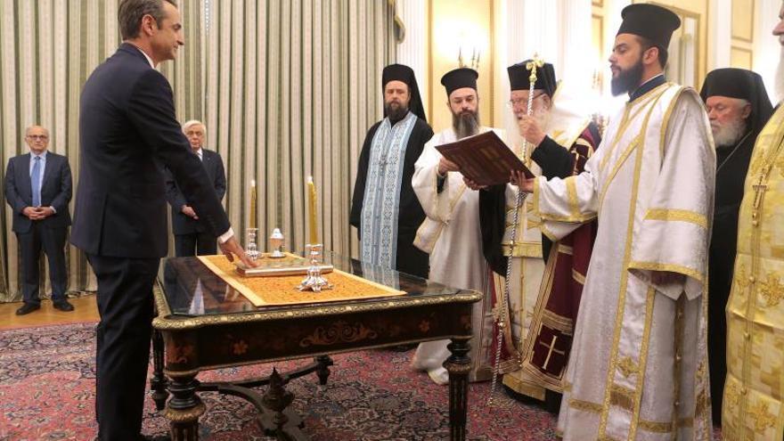 Kyriakos Mitsotakis jura como primer ministro ante el arzobispo de Atenas, Jerónimo II, y varios representantes de la iglesia ortodoxa.