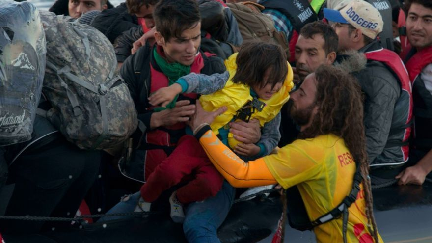 Un socorrista catalán de Proactiva toma en brazos a un niño refugiado a su llegada a Lesbos / Juan Carlos Mohr