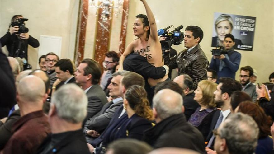 Militante de Femen con los pechos al aíre interrumpe un mitin de Le Pen