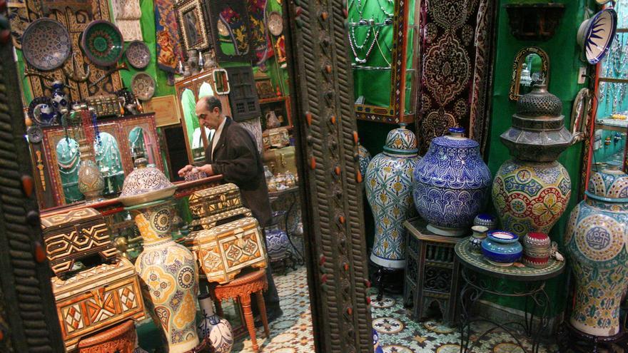 Un vendedor de cerámica tradicional inspecciona la mercancía en una tienda de la medina de Fez. Viajar Ahora