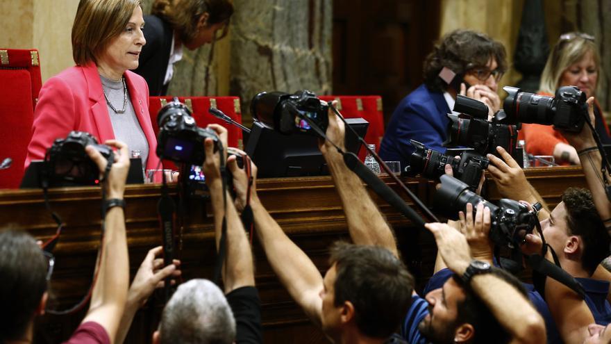 Los fotógrafos cercan a Carme Forcadell en el inicio del pleno del Parlament.
