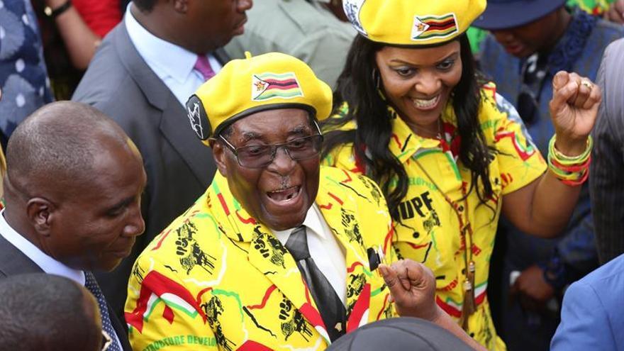 El expresidente de Zimbabue, Robert Mugabe, y su mujer, Grace, saludan durante una concentración celebrada por simpatizantes para mostrarle su apoyo en la capital el 8 de noviembre.