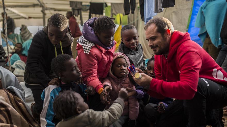 Marc, capitán del Open Arms durante la misión 57 de la ONG, reparte bolígrafos y papeles a algunos de los niños rescatados para que puedan dibujar / Olmo Calvo