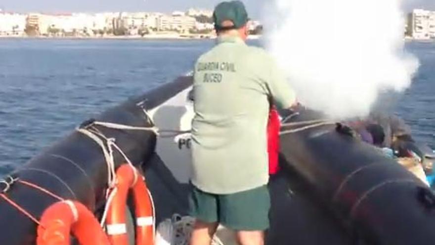 Pantallazo del vídeo donde se muestra a un Guardia Civil vacía un extintor sobre una patera de inmigrantes.