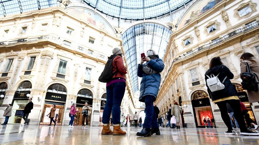 Dos turistas con mascarillas sacan fotografías en la Galería Vittorio Emanuele II durante el brote de coronavirus