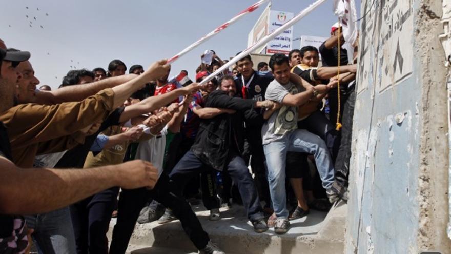 Manifestantes iraquíes en 2011 tratando de derribar un muro de la Zona Verde controlada por EEUU. En la misma época en Siria estallaban las revueltas