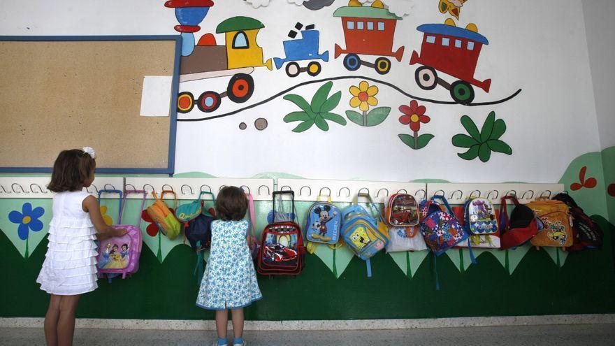 Dos niñas frente a las perchas de una escuela infantil