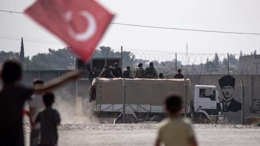 Varios niños ondean la bandera turca mientras saludan a los soldados sirios apoyados por Turquía que se dirigen al norte de Siria,en Sanliurfa (Turquía)