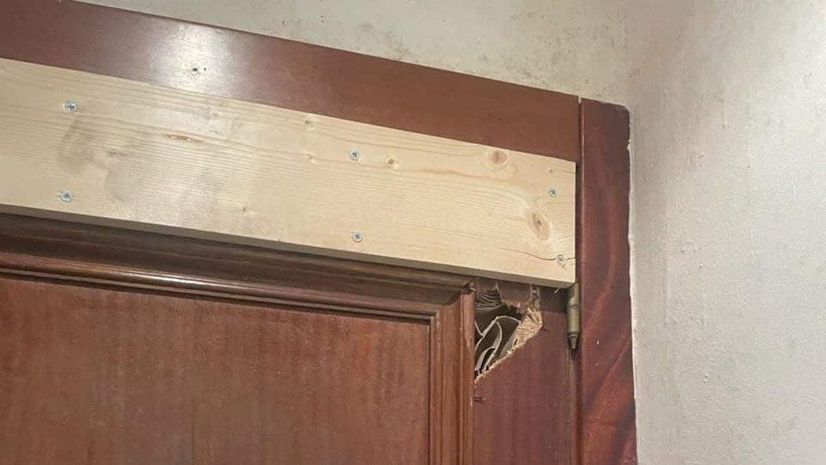 Puerta de la vivienda en la que son apreciables destrozos y el refuerzo aplicado.