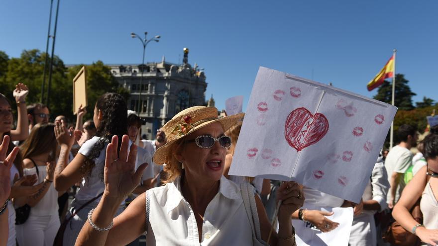 Una mujer porta una pancarta con símbolos a favor del diálogo