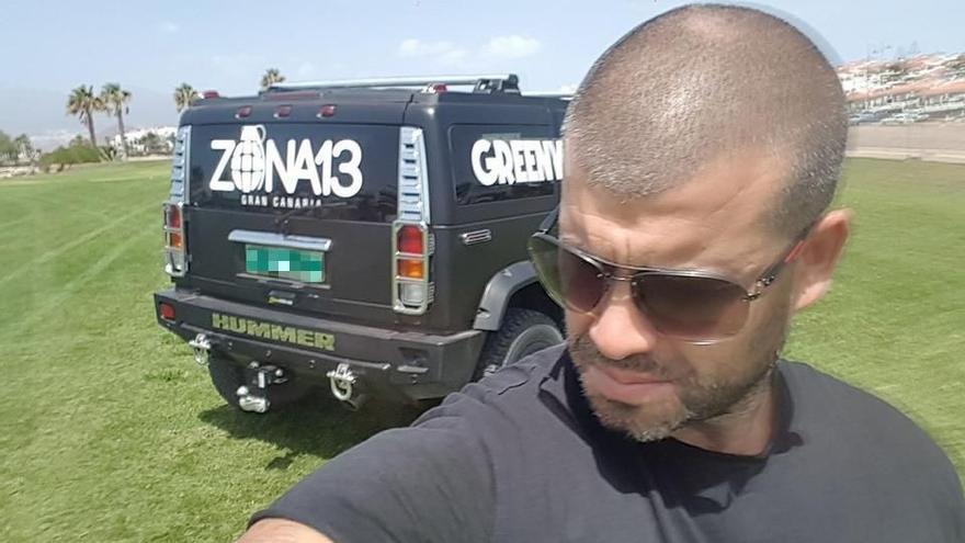 Samuel Yebra posando en un todoterreno Hummer serigrafiado con el logo del local.