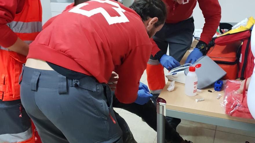 Voluntarios de Cruz Roja atienden a un migrante llegado en patera a las costas alicantinas